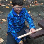 Boy sawing wood at Caulbridge School