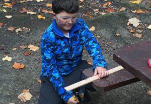 Boy sawing wood at Caulbridge School